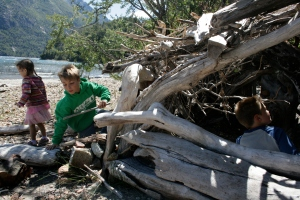 Playing in a driftwood shelter on the beach near Llao Llao